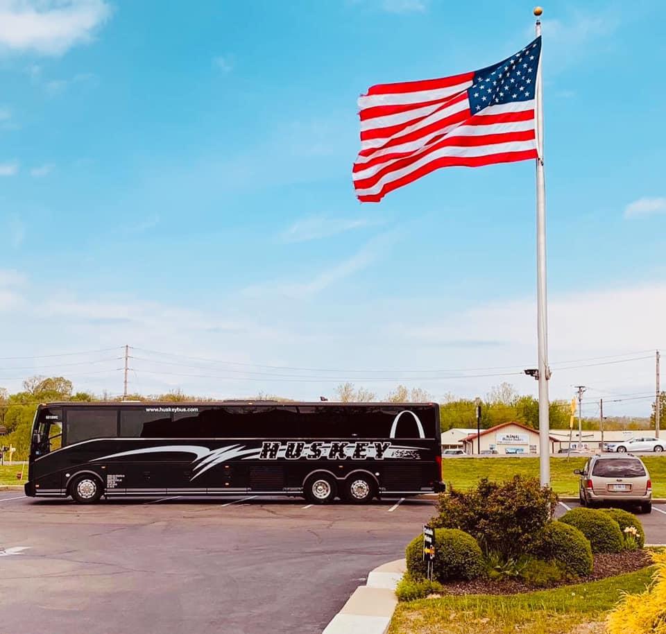 Huskey Bus sitting under an American Flag